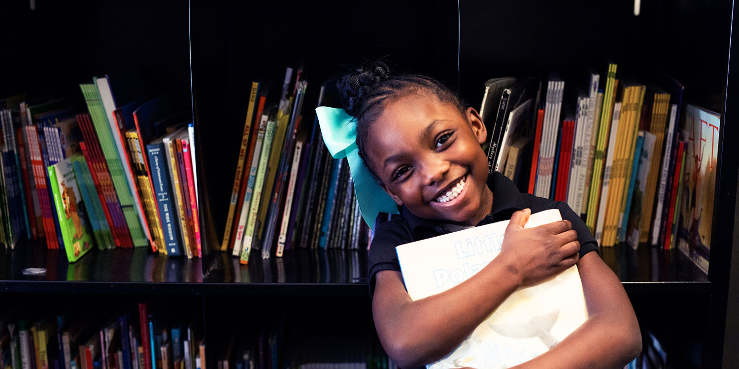Smiling student holding a book.